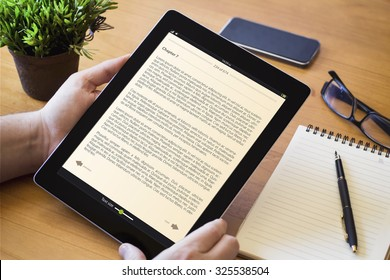 hands of a man holding a book device over a wooden workspace table. All screen graphics are made up.