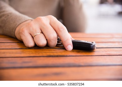 Hands of man holding the car keys on wooden table