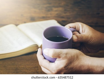 hands of man holding  a cup of coffee over  holy bible on wooden table background