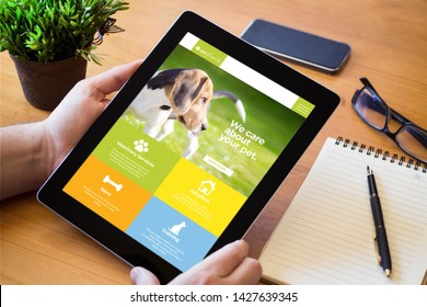 hands of a man holding a pet website device over a wooden workspace table. All screen graphics are made up.