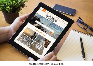 hands of a man holding a travel agency website on screen device over a wooden workspace table. All screen graphics are made up.
