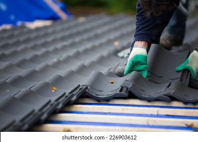 Hands of a man laying tiles on the roof while roofing a house near the city of Breda, Netherlands, Europe, in a traditional craftsman way
