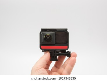 in the hands of a man modern panoramic action camera aimed at it, white background. copy space.