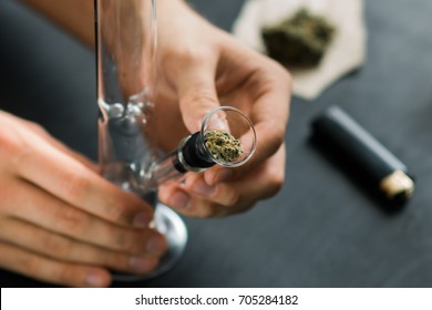 Hands of a man on Bong and medical marijuana, cannabis thc flower Sativa and Indica Close up on a black background. lifestyle Concepts the legalization of marijuana in the world