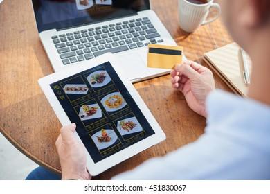 Hands of man ordering Asian food on website
