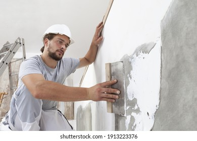 Hands man plasterer construction worker at work with trowel, plastering a wall, closeup