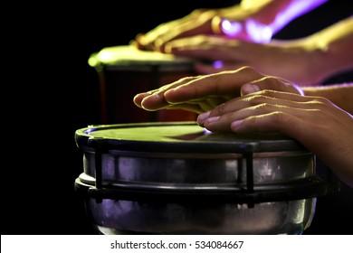Hands of man playing African drum on dark background