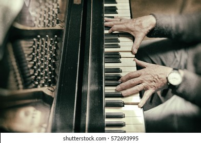 Hands of man playing piano with a big watch and old style photograph with blurry effects