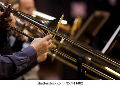 Hände von Menschen, die Posaune im Orchester spielen