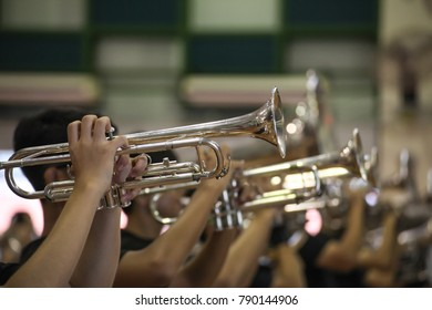 Hands of man playing the trumpet in marching band