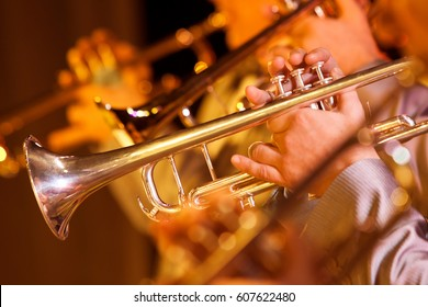 Hands of man playing the trumpet in the orchestra closeup