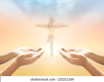 Hands of man praying over blurred crown of thorns and Jesus Christ on the cross over a colorful sunset background