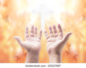 Hands of man praying over blurred the cross on beautiful autumn background.