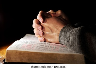 Hands of a man praying in solitude with his Bible (Christian image, shallow focus).