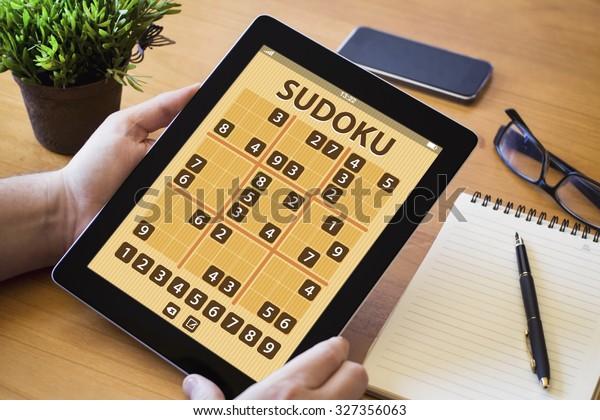 manos de una procastina de hombre que sostiene un dispositivo sudoku sobre una mesa de trabajo de madera. Todos los gráficos de pantalla están compuestos.