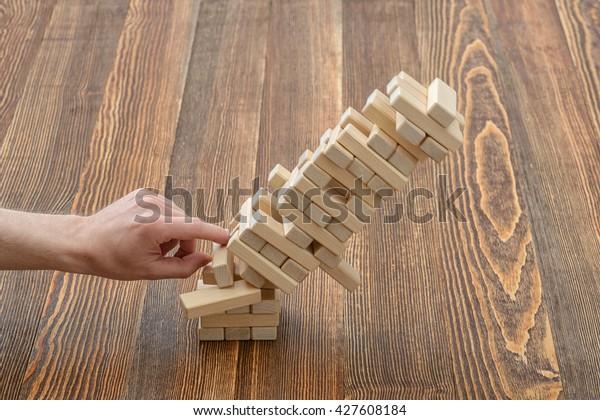 Руки человека толкнули кирпич и разрушили башню. Джанга. Фото крупным планом. Дисбаланс. Свал и разрушение. Ошибка. Развлекательная деятельность. Игра физического и умственного мастерства. Удаление блоков