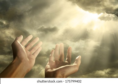Hands of a man reaching to towards sky