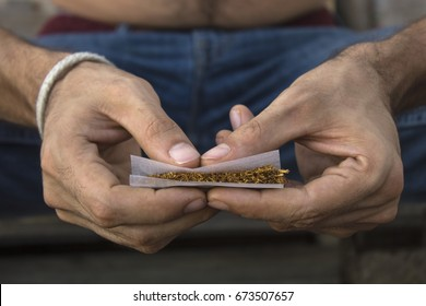 Hands of man rolling a joint