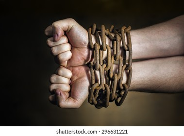 Hands of a man with a rusty chain around the wrists.
