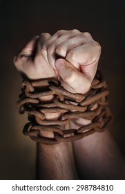 Hands of a man with a rusty chain around the wrists. Short depth of field, the sharpness is in the fist.