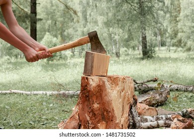 Hands of a man splitting wood with an axe