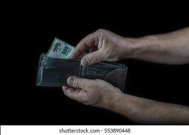 hands of man taking a five hundred Argentine peso bill from a wallet, on a black background