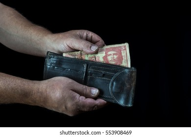 hands of man taking a three cuban peso bill from a wallet, on a black background