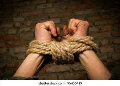 Hands of man tied up with rope against brick wall