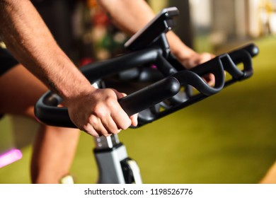 Hands of a man training at a gym doing cyclo indoor. Sports and fitness concept.
