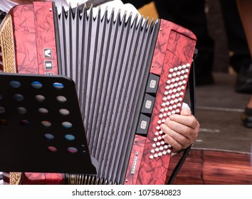 hands of man using accordion