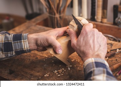 Hands of a man using a knife to carve a small piece of wood on a workbench