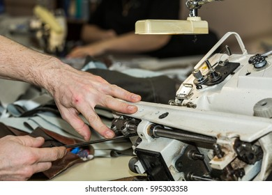 Hands of a man who repairs sewing machine