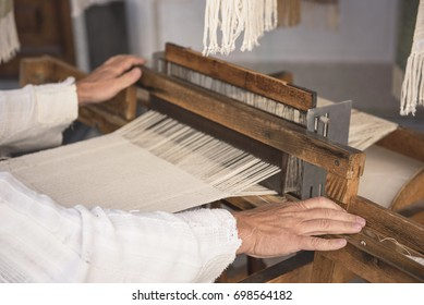 Hands of a man who weaves on a loom