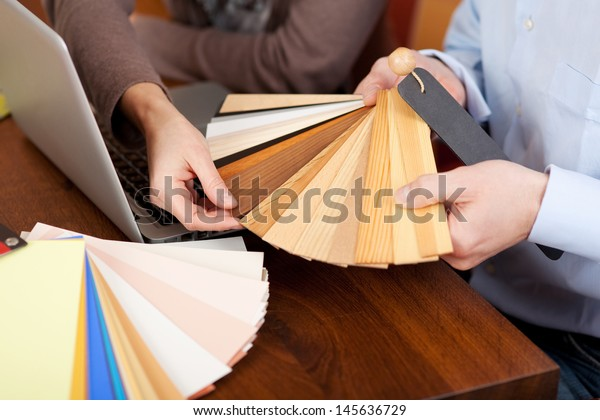 Hands of a man and woman choosing timber samples for the house during a renovation project