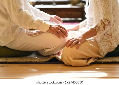 The hands of a man and a woman facing each other in lotus posture, meditating, concept.