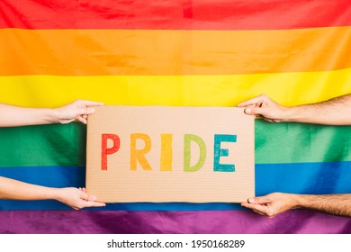 hands of man and woman holding a cardboard with the word pride written in colors on the background gay pride flag