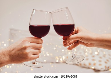 Hands of a man and a woman are holding glasses of wine. Romantic atmosphere, soft focus, bokeh, close-up
