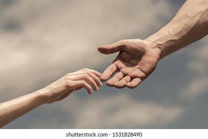 Hands of man and woman on blue sky background. Lending a helping hand. Giving a helping hand. Solidarity, compassion, and charity, rescue. Hands of man and woman reaching to each other, support.