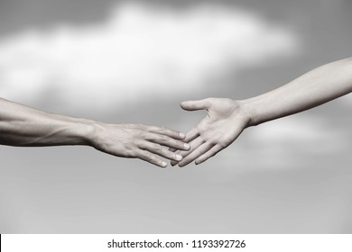 Hands of man and woman reaching to
