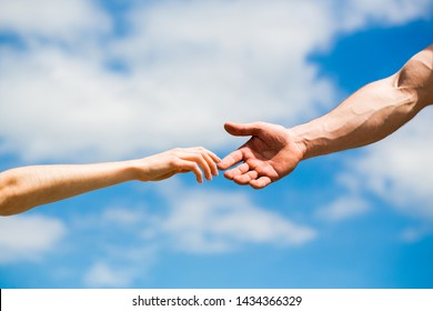 Hands of man and woman reaching to each other, support. Hands of man and woman on blue sky background. Giving a helping hand. Lending a helping hand. Solidarity, compassion, and charity, rescue.
