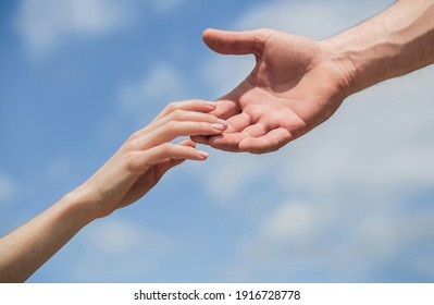 Hands of man and woman reaching to each other, support. Solidarity, compassion, and charity, rescue. Giving a helping hand. Hands of man and woman on blue sky background. Lending a helping hand.