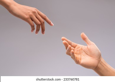 Hands of man and woman reaching to each other