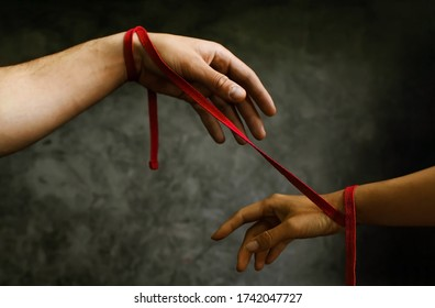 The hands of a man and a woman are tied with a red thread, a symbol of fate.