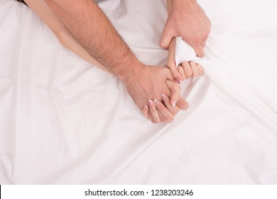 Hands of man and woman who having sex in bed on white crumpled sheet, focus on hands, close up. Man grasping woman.
