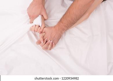 Hands of man and woman who making love in bed on white crumpled sheet, focus on hands, close up. Man grasping woman.