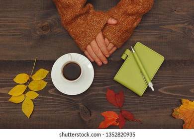 Hands of man at a wooden table with a cup of coffee and a notebook with pen