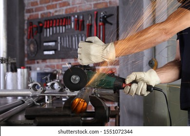 hands man work in home workshop garage cut metal pipe, with construction gloves, cutting metal makes sparks closeup, diy and craft concept
