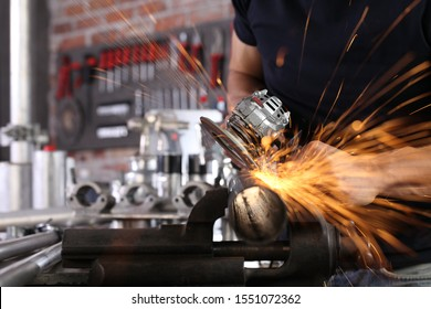 hands man work in home workshop garage with angle grinder, sanding metal makes sparks closeup, diy and craft concept