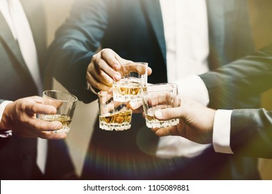 Hands of mans with glasses of whiskey, celebrating and toasting