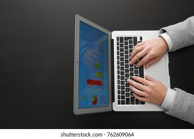Hands of marketing manager working with laptop on dark background